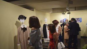 Visitantes de la exposición contemplan los uniformes expuestos.